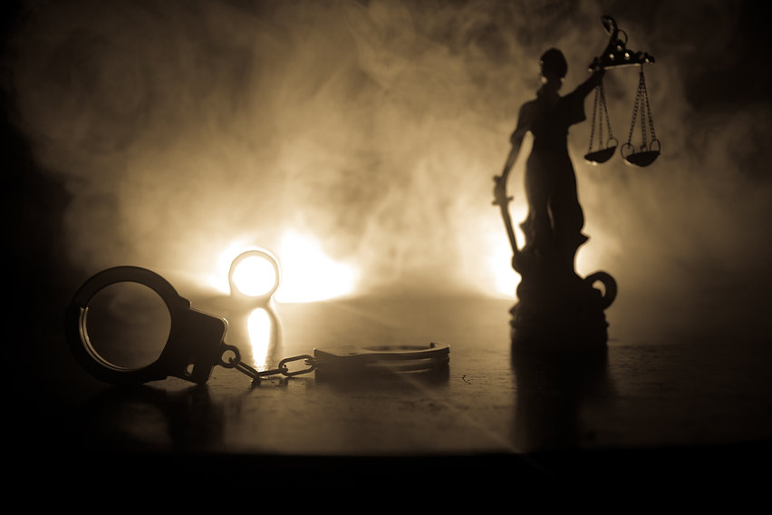 Legal law concept. Silhouette of handcuffs with The Statue of Justice on backside with the