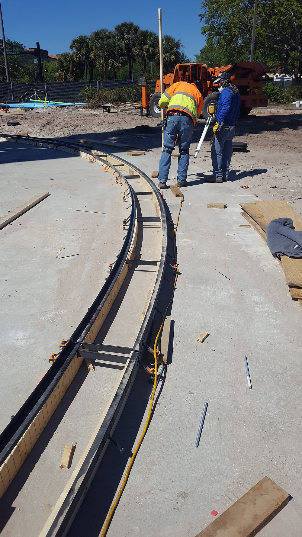 This contractor is hand forming a radius trench drain at the base of the Star Flier amusement park ride.