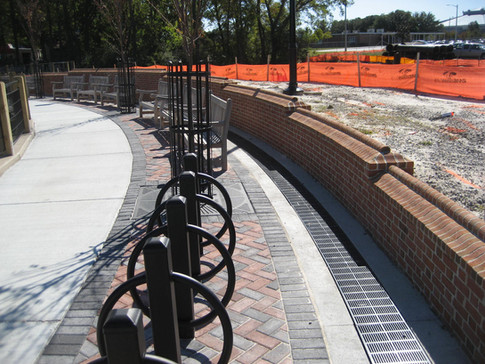 Trench drain in park next to brick wall
