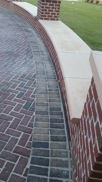 Curved patio slot drain next to brick seating wall.