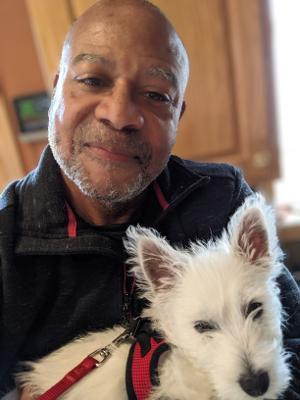 smiling man holding Westie puppy
