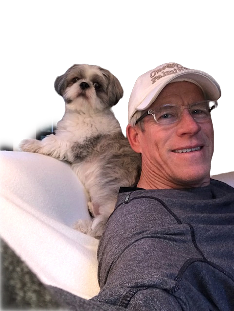Man on couch with baseball hat and shih tzu dog perched on the back of the couch
