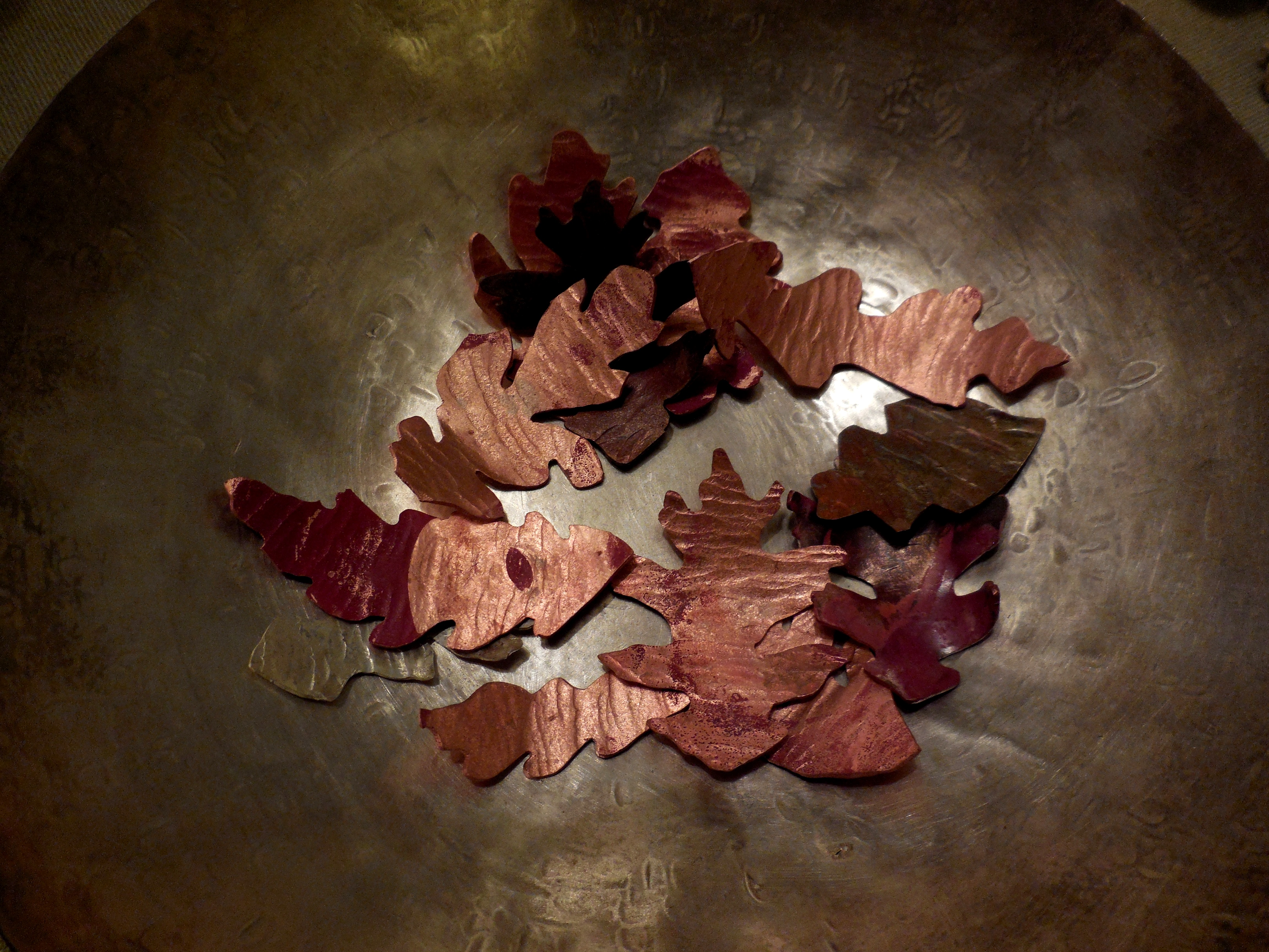 copper leaves in a silver bowl