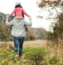 girl-riding-parent-shoulders-travel-safety.jpg