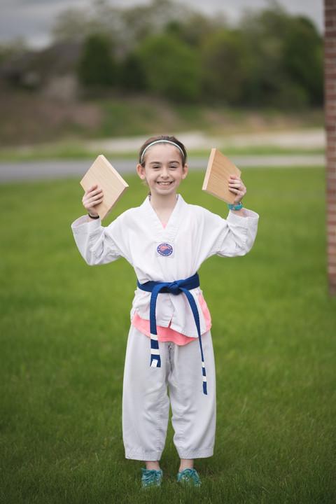 Blue belt girl holding broken boards