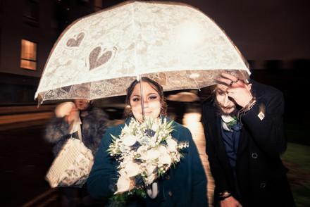 A portrait wedding photo of the couple hiding under an umbrella