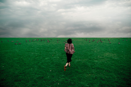 A young woman running in a green field