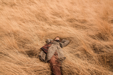 A portrait photo of a young woman lying on high yellow grass in a field