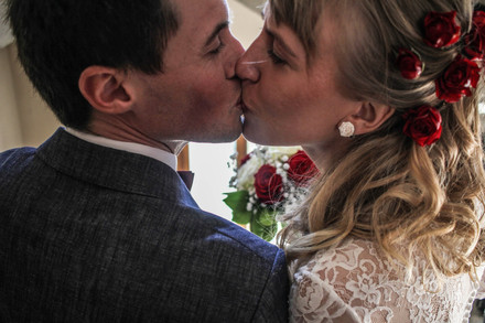 Wedding portrait photo of a kissing couple in a registry office