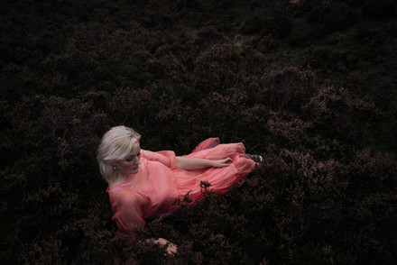 portrait photo of a woman in a pink dress in dark bushes in a park in manchester