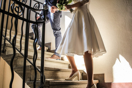 couple going up the stairs in a registry office on their wedding