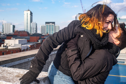 a portait photo of a happy couple on a rooftop in manchester