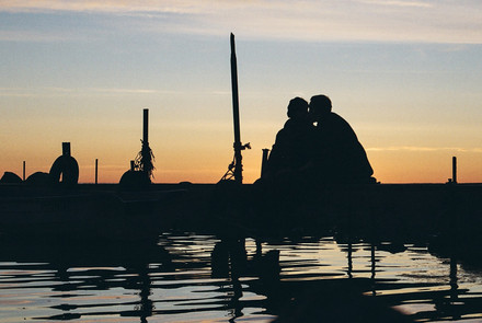 a silhouette of a couple on a pier at a sunset