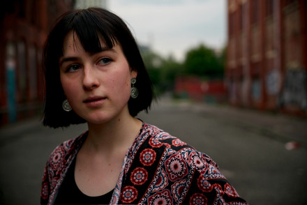 Headshot portrait of a young woman on an empty street in Manchester