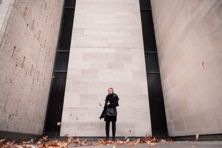 A portrait of a young woman in manchester in front of a concrete wall