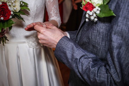 A groom puts the wedding ring on brides hand photo by Fedor Vasilev in Manchester