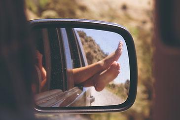 Feet relaxing out a car window