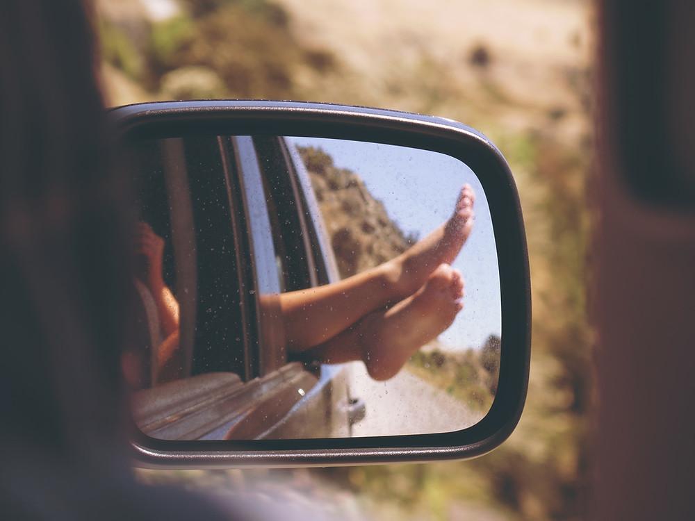 pieds se refletant dans un miroir de voiture
