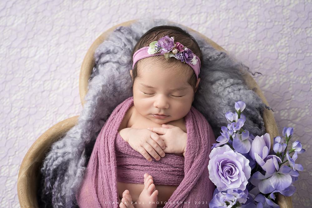 newborn baby girl posed purple heart flowers