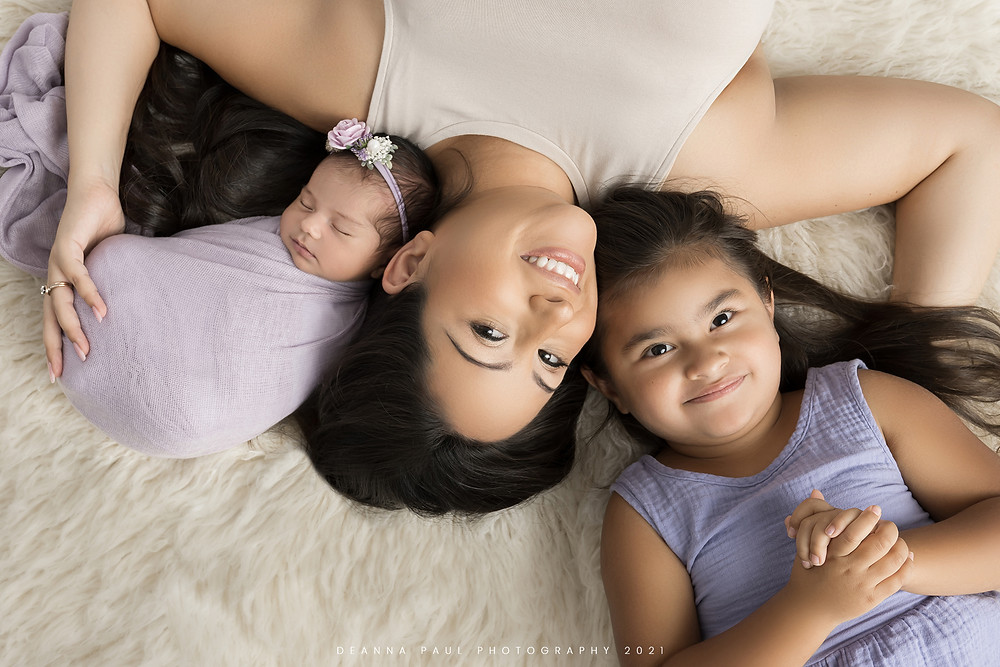 mother with two daughters newborn session