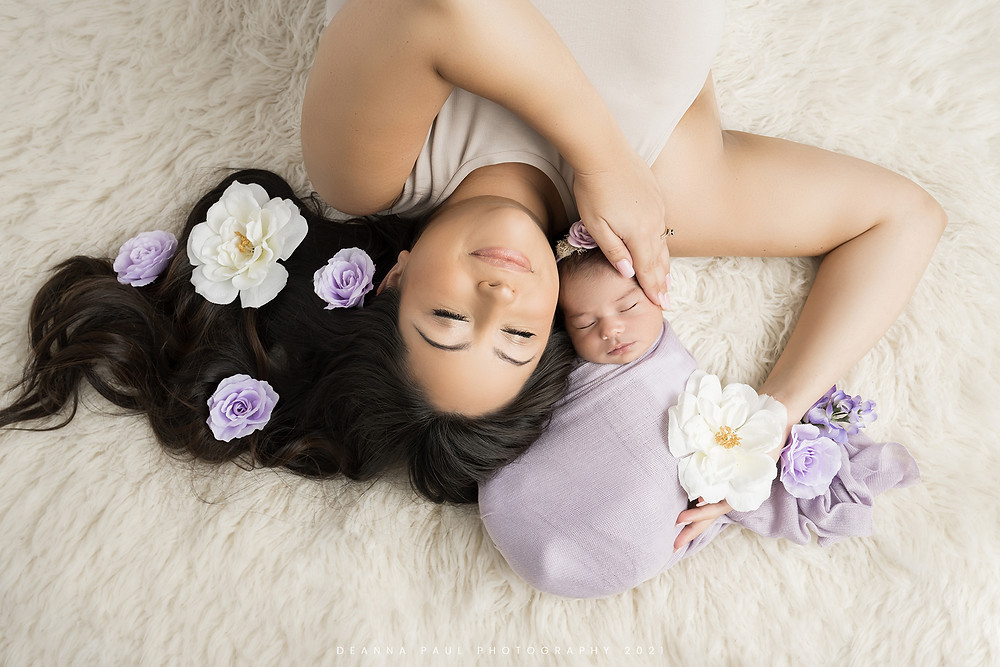 newborn baby girl posed baby with mother purple flowers