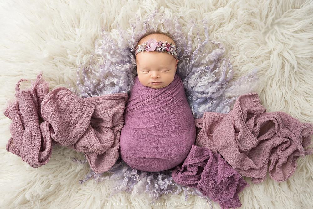 newborn baby girl purple swaddled