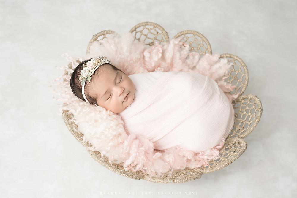 newborn baby girl in basket pink
