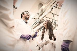 Four adults in lab coats in an industrial setting