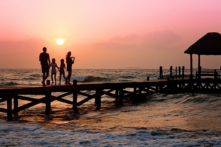 family-on-a-pier-over-pink-sunset-backgr