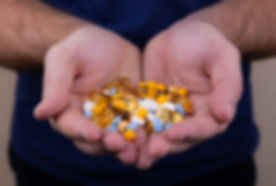 Group of pills held by two open hands