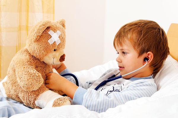 a sick child examined teddy with stethos