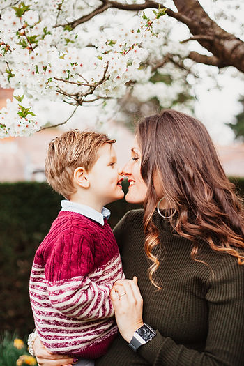 Mother and son touching noses under blossom tree