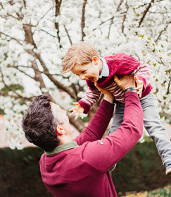 Father swinging smiling boy into the air