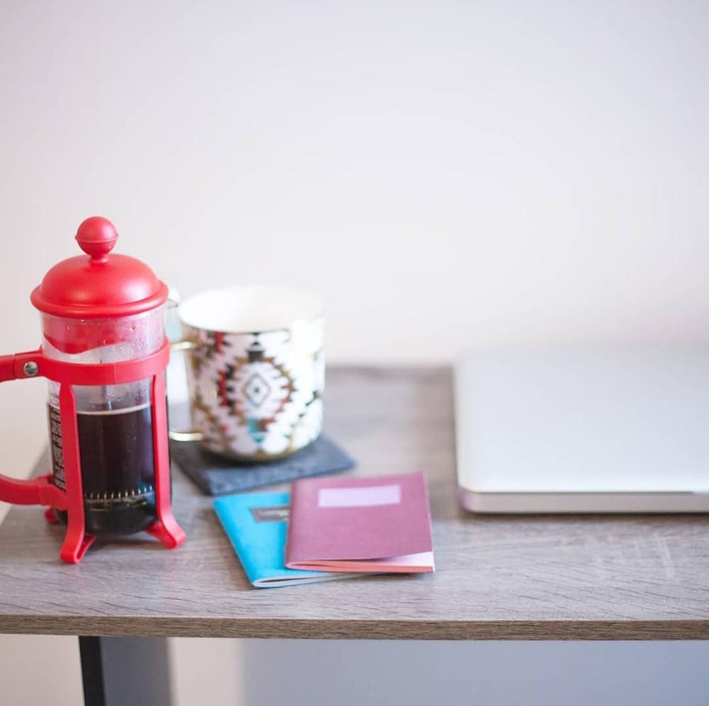 Coffee, mug, notebooks on a desk