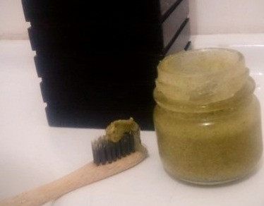 Pequeno vidro contendo pasta dental e escova ao lado