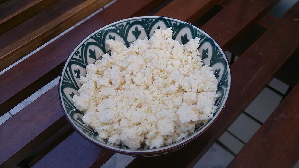 queijo servido em tigela de cerâmica sobre banco de madeira