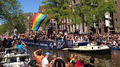 Amsterdam canal pride, rainbow flag, hot gay boy on the boat.
