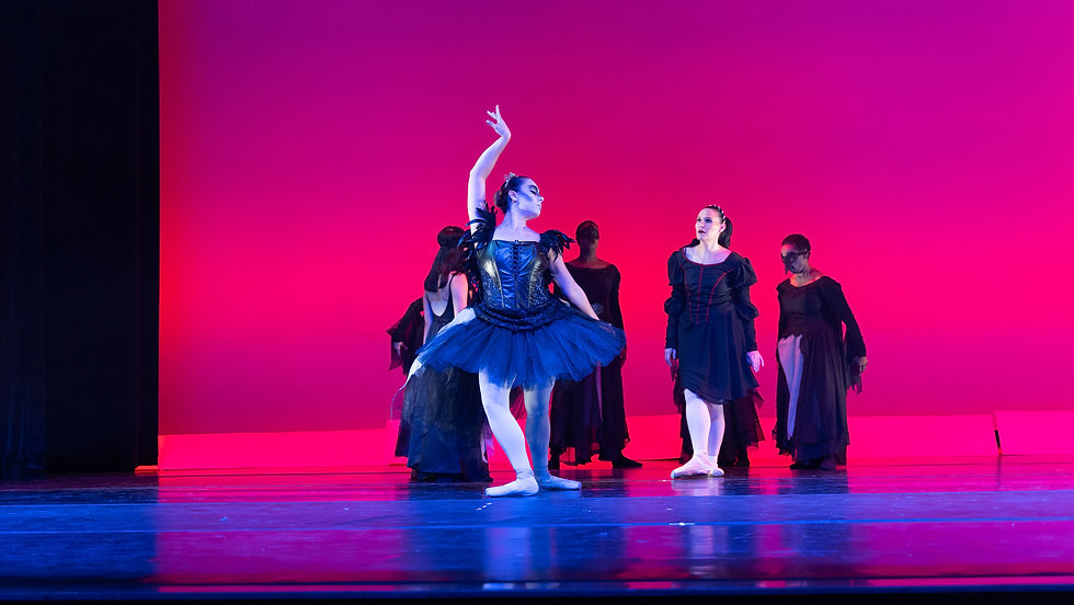 A ballet dancer looking at a female dancer that is dressed as the Raven Queen