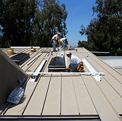 Roofers installing a standin seam metal roof