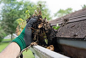 cleaning rain gutters from dirt and leaves