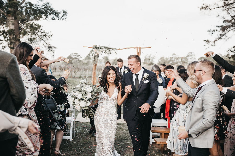 South Coast Wedding and family photograper. a couple running through confetti after getting married