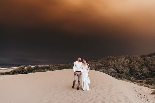 Couple standing on a beach in the middle of bush fire season on the south coast. While bush fire is burning futher down the south coast. Shot by Wedding, family and elopement photographer matt ashton photography