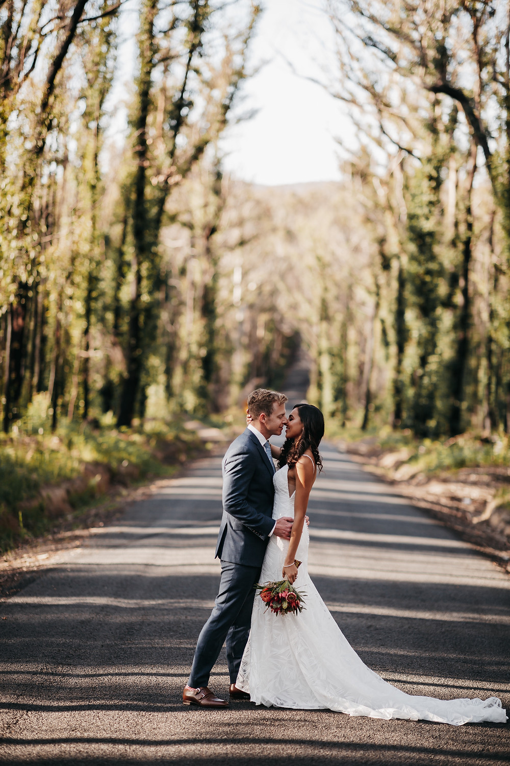 South Coast Elopement Photographer Matt Ashton Photography. a couple standing in the middle of the road which has been affected by a recent bush fire.