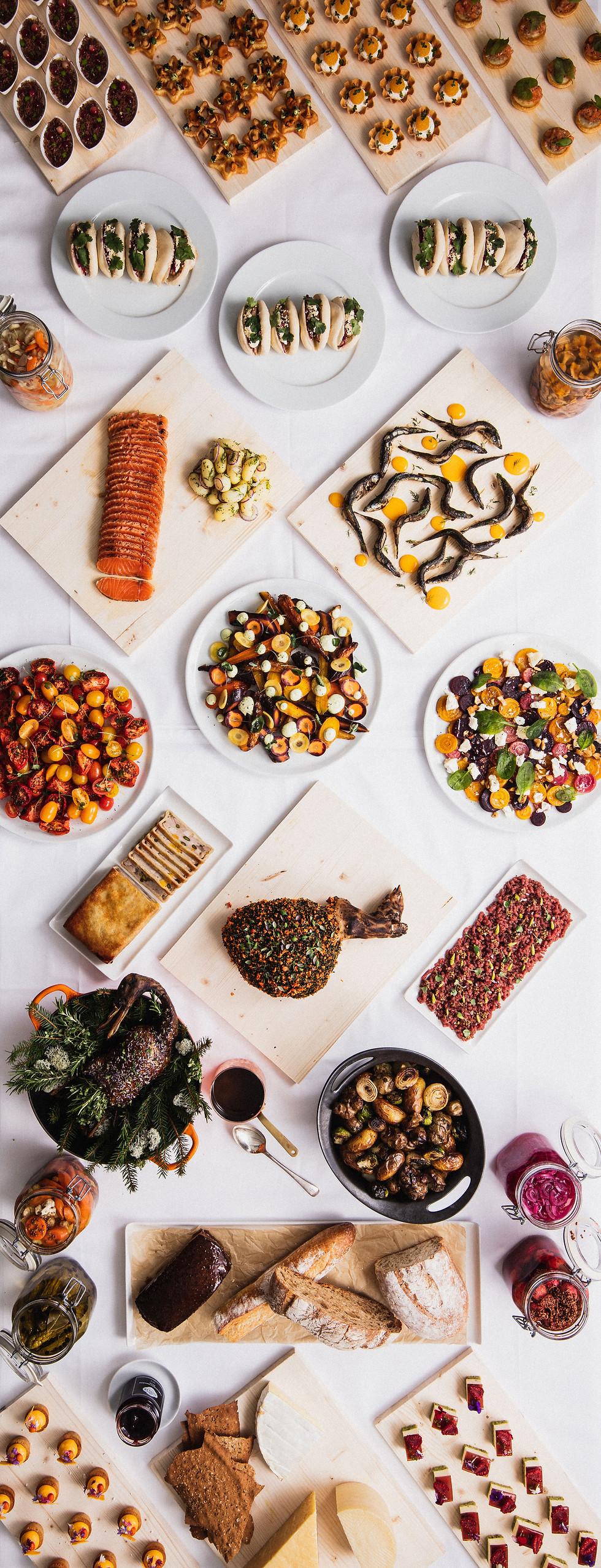 Buffettipöytä, jossa on monenlaista kauniisti katettua ruokaa, erilaisia cocktailpaloja, steam buneja, paahdettua lohta, savustettuja muikkuja,salaatteja, tartar-lautanen, kokonainen paahdettu sorsa, paahdettuja perunoita ja artisokkia, erilaisia säilykkeitä purkissa.