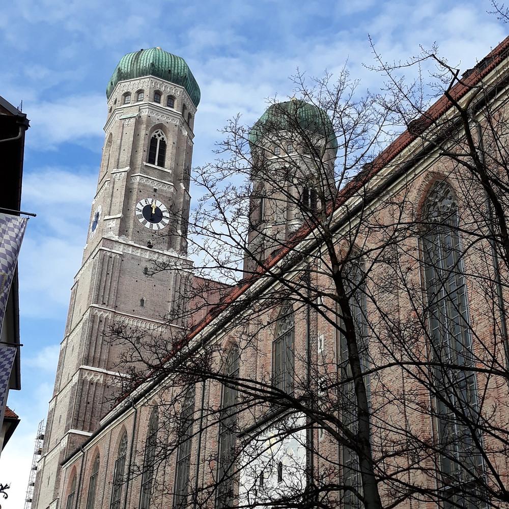 As torres da Frauenkirche em Munique contra o céu azul.