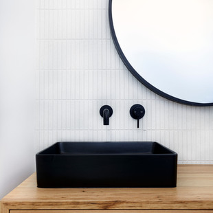 The warmth of the Blackbutt vanity is balanced by the striking black handbasin and tapware with textured white finger tile splashback. Photography by www.philgallagher.com