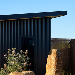The dark colour scheme of the facade of this home contrasts with the bright white interiors. Custom orb cladding in Colorbond Monument with Steel Roof Fascia to match. Photography by www.philgallagher.com