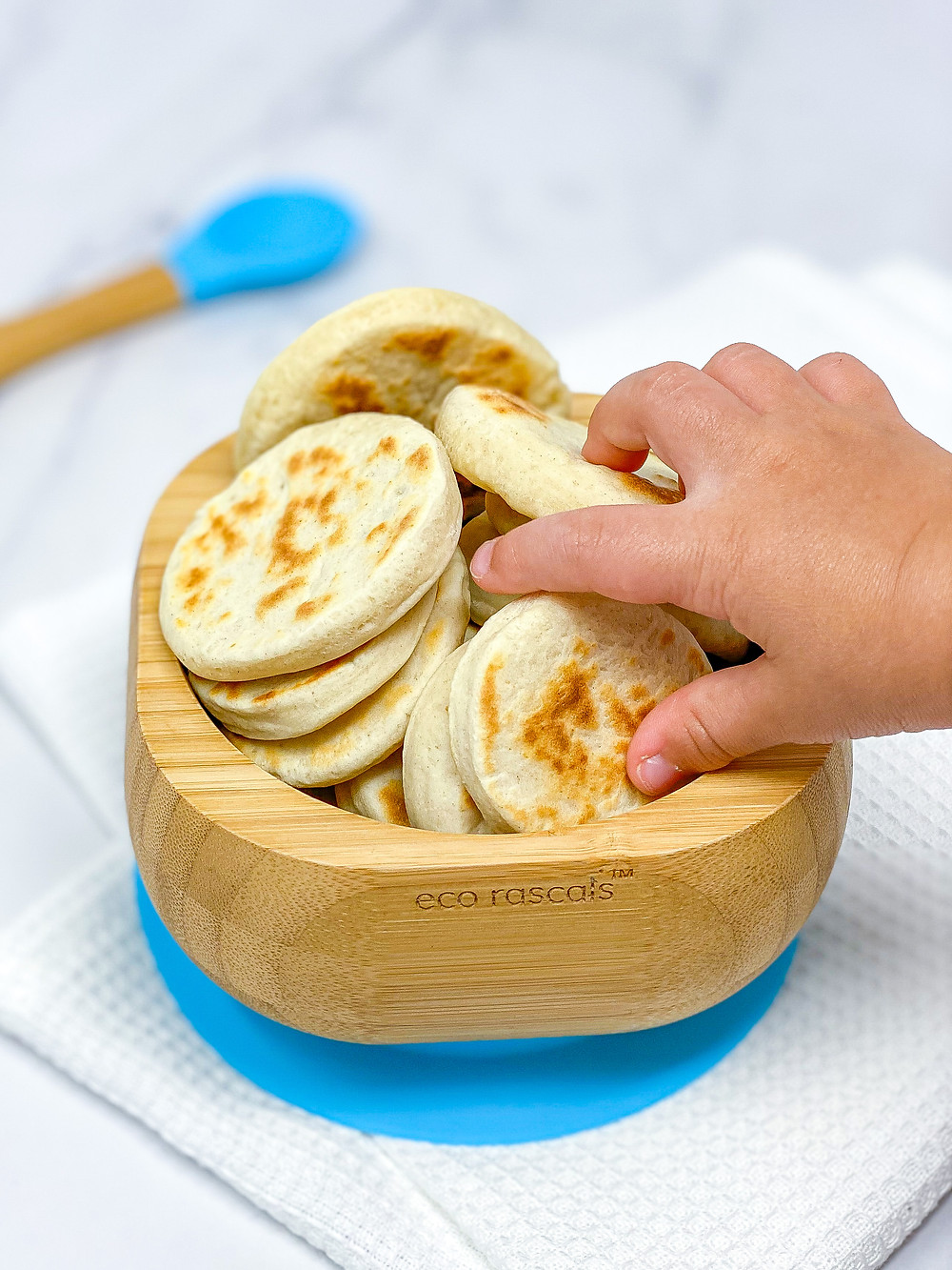 BABY FLATBREAD with little hand in bamboo plate