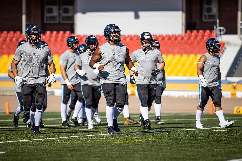 Murilo de capacete e roupa de treino com companheiros de time se deslocando para iniciar uma jogada