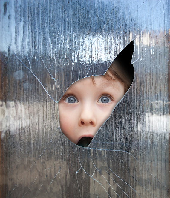 boy looks through a broken window.jpg